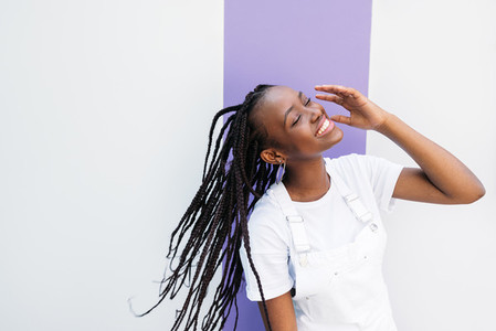 Young beautiful female in white overalls having fun with closed eyes at wall