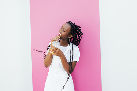 Happy woman drinking juice while dancing at white wall with pink stripe