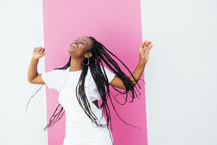 Happy girl in white clothes dancing and having fun at white wall with pink stripe