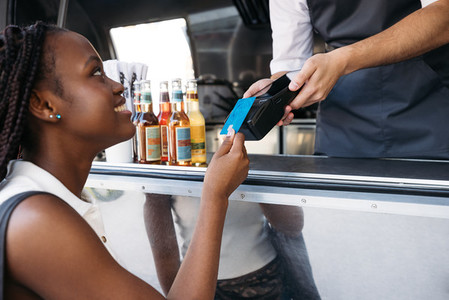 Close up of smiling woman paying with a credit card while standing at a food truck
