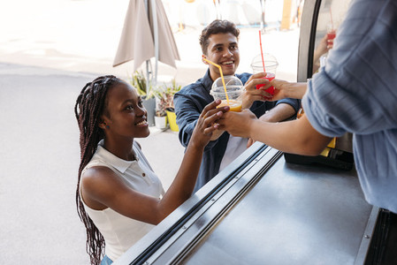 Two smiling customers receiving juice from unrecognizable saleswoman at a food truck