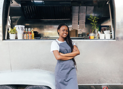 Confident woman in apron standing at her food truck with crossed arms