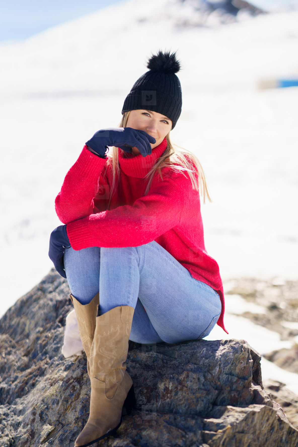 Young woman sitting on a rock in the snowy mountains in winter  in Sierra Nevada  Granada  Spain