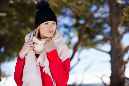 Young blonde woman in a snowy forest in the mountains in winter  in Sierra Nevada  Granada  Spain