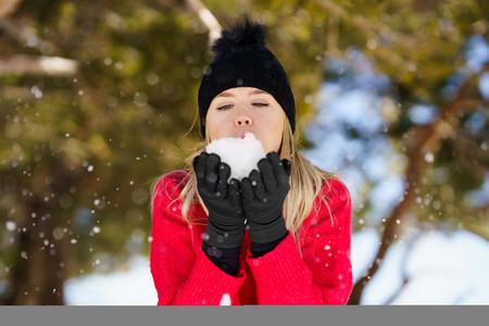 Blonde woman blowing a snowball in winter  in Sierra Nevada  Granada  Spain