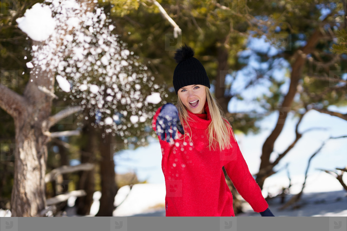 Young woman throwing snowballs forward in a snow covered forest in the mountains
