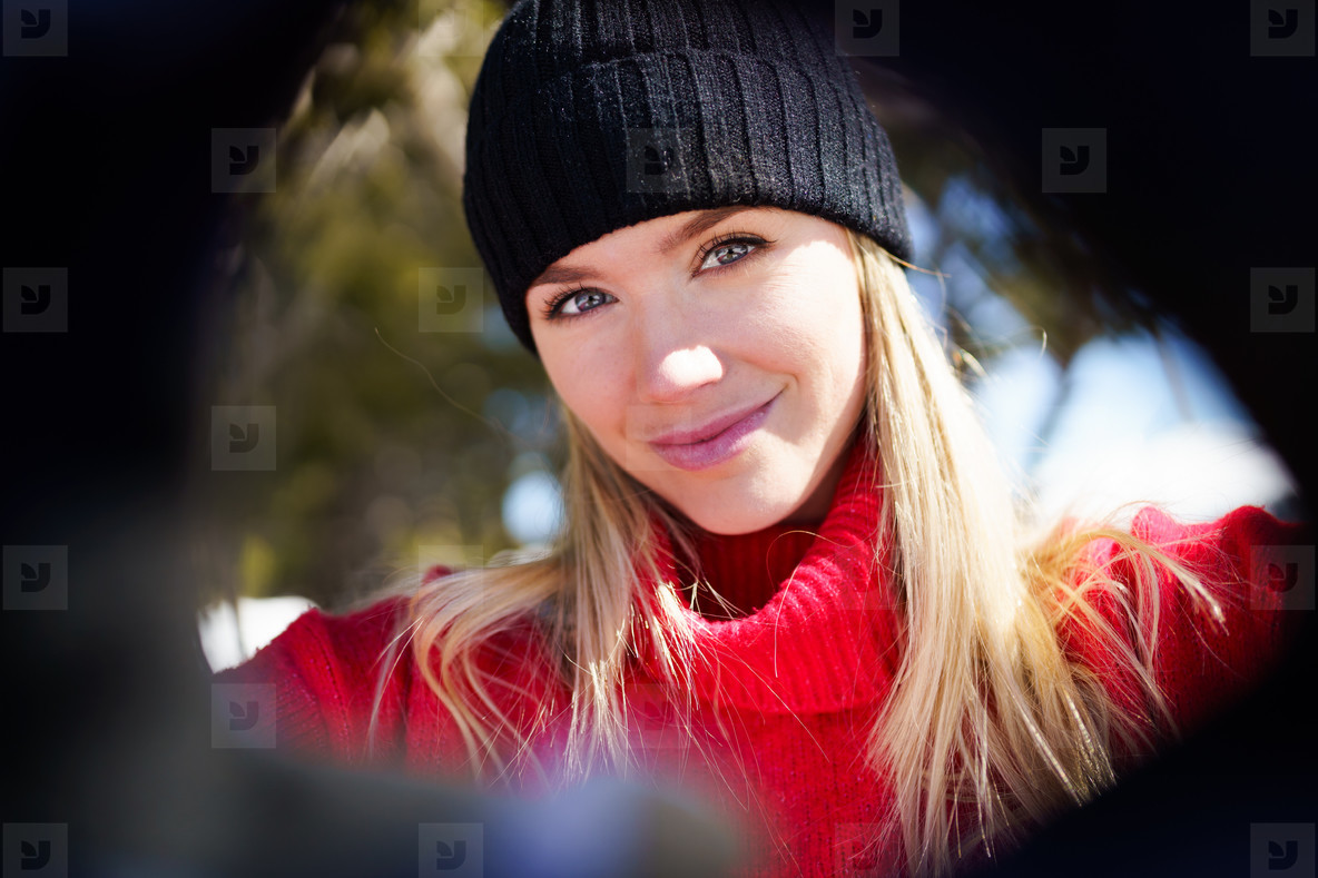 Young blonde woman taking a selfie in a snowy mountain forest in winter