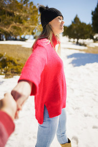 Blonde woman in winter clothes walking holding her partners hand in the snowy mountains