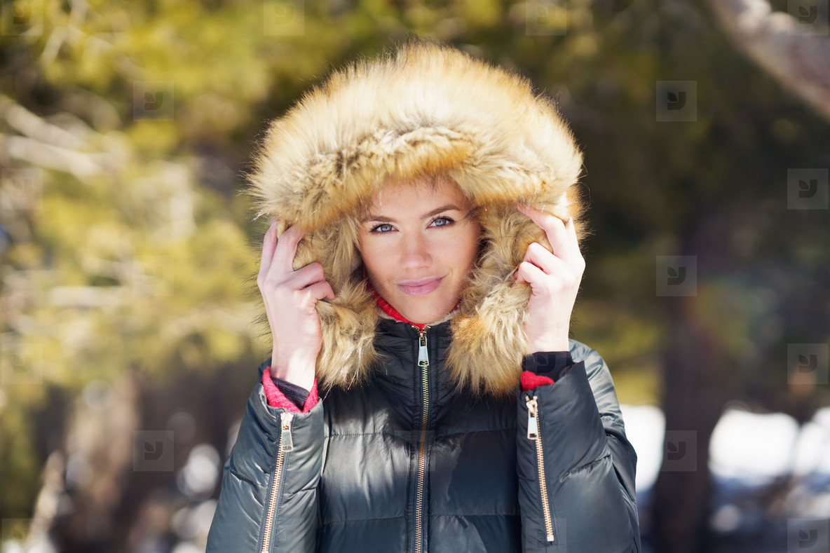 Young woman wearing a furry hooded jacket enjoying the snowy mountains in winter