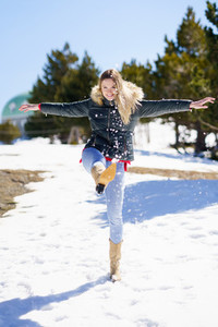 Blonde happy woman kicking snow in a snow covered forest in the mountains