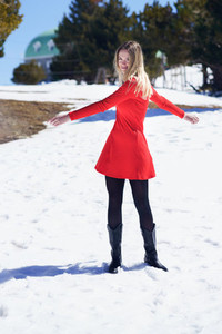 Woman wearing a red dress and black stockings opening her arms in happiness in the snowy mountains