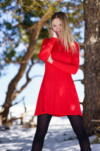Young blonde woman wearing a red dress and black stockings in the snowy mountains in winter