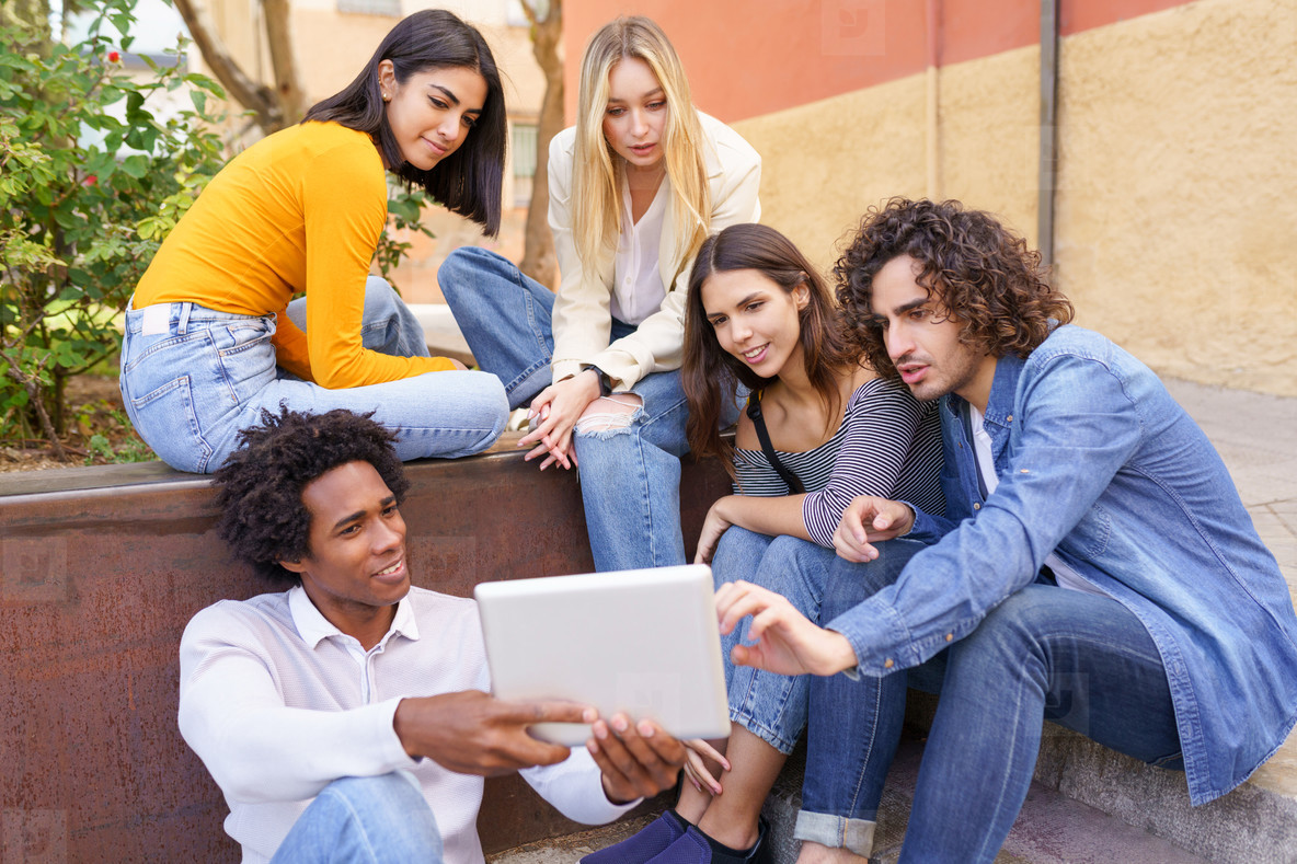Multi ethnic group of young people looking at a digital tablet outdoors in urban background