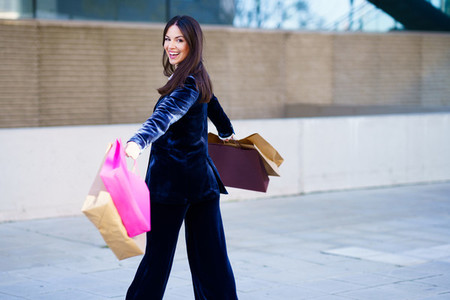 Happy woman turning with joy for her purchases in shopping bags