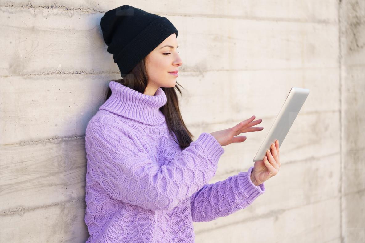 Female student in her twenties using digital tablet outdoors