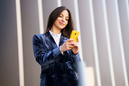 Business woman wearing blue suit using smartphone in an office building