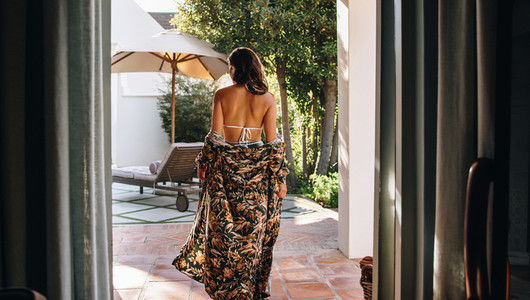 Rearview of a woman in a gown and a bikini at a spa resort