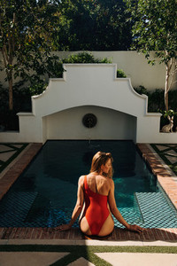 Gorgeous tourist woman sitting alone by the pool