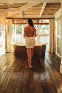 Woman going for a luxury bath in a hotel room