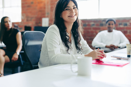Creative businesswoman smiling while sitting in a modern office