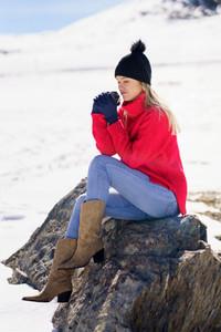 Blonde woman sitting on a rock in the snowy mountains in winter  in Sierra Nevada  Granada  Spain