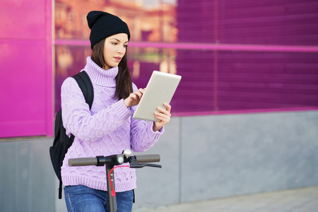 Woman in her twenties with electric scooter using digital tablet outdoors