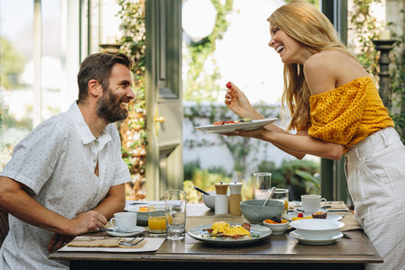 Romantic woman going in to feed her husband during breakfast
