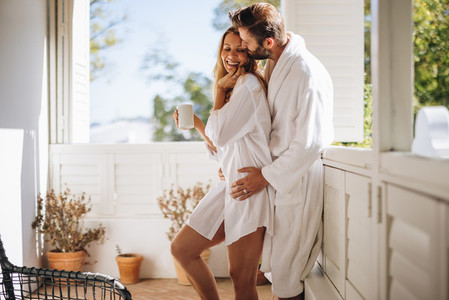Affectionate couple flirting on a balcony