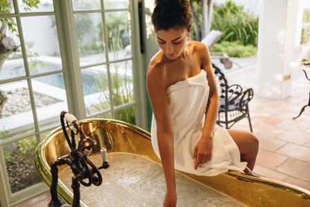 Glamorous young woman preparing a bath at a spa resort