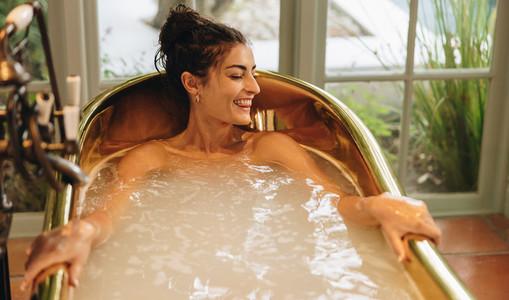 Smiling young woman enjoying a refreshing bath