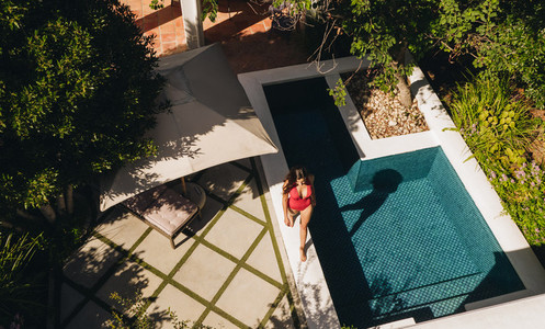 Aerial view of a young woman walking next to a pool in a swimsui