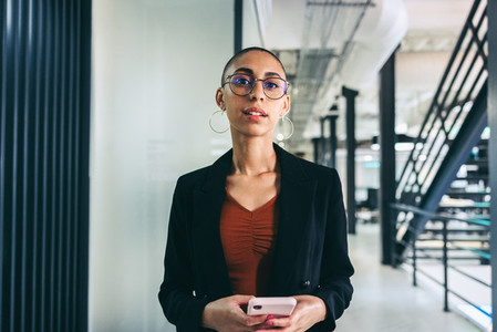 Young businesswoman holding a smartphone in an office