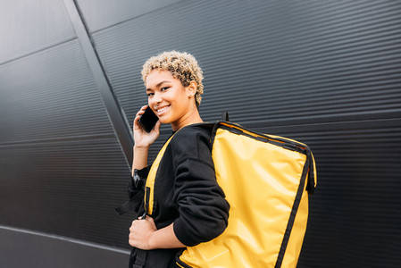 Woman courier with backpack talking on cellphone and looking at camera against the black wall