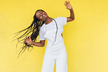 Cheerful woman wearing white overall dancing at yellow wall