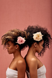 Two women with flowers in their hairs standing back to back at a pink wall with closed eyes