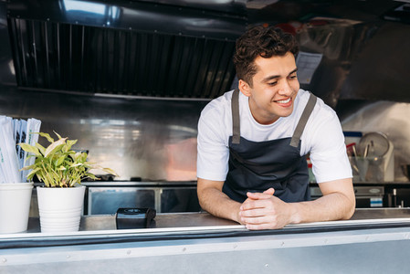 Handsome food truck owner in apron leaning on the counter looking down