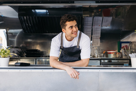 Young salesman in apron looking away from food truck window