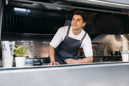Portrait of a smiling food truck owner wearing apron leaning counter