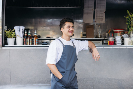 Side view of smiling waiter standing at food truck and looking away