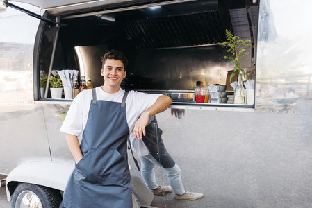 Portrait of a confident salesman leaning on a food truck looking at camera