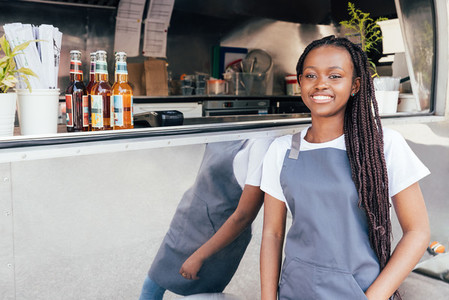 Smiling waitress with long braids leaning on food truck looking away