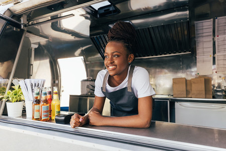 Smiling saleswoman in apron leaning counter standing in a food truck