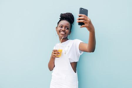 Happy woman in white casuals taking selfie holding orange juice
