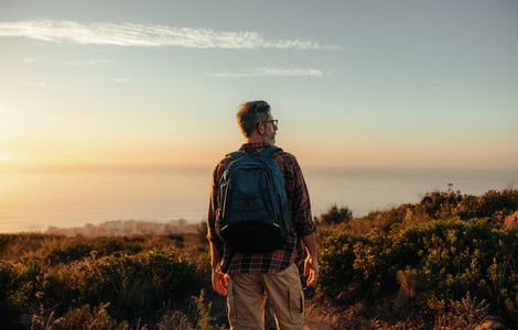 Mature backpacker looking at the view on a hilltop