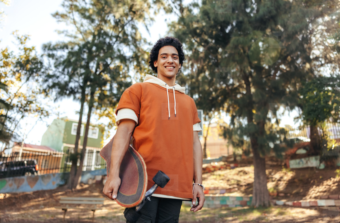 Carefree skateboarder holding his skateboard in an urban park