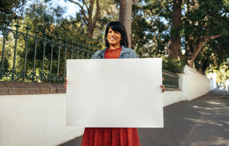 Smiling woman holding a blank placard outdoors