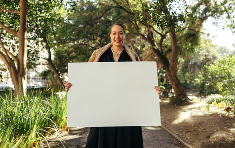 Cheerful posh woman holding up a white placard outdoors