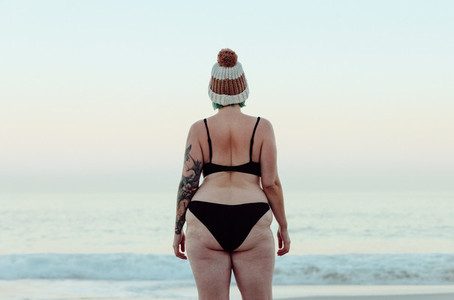 Anonymous winter bather standing at the beach