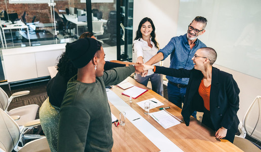Confident group of businesspeople bringing their fists together