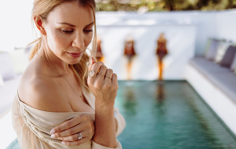 Woman taking off her dress in front of a pool